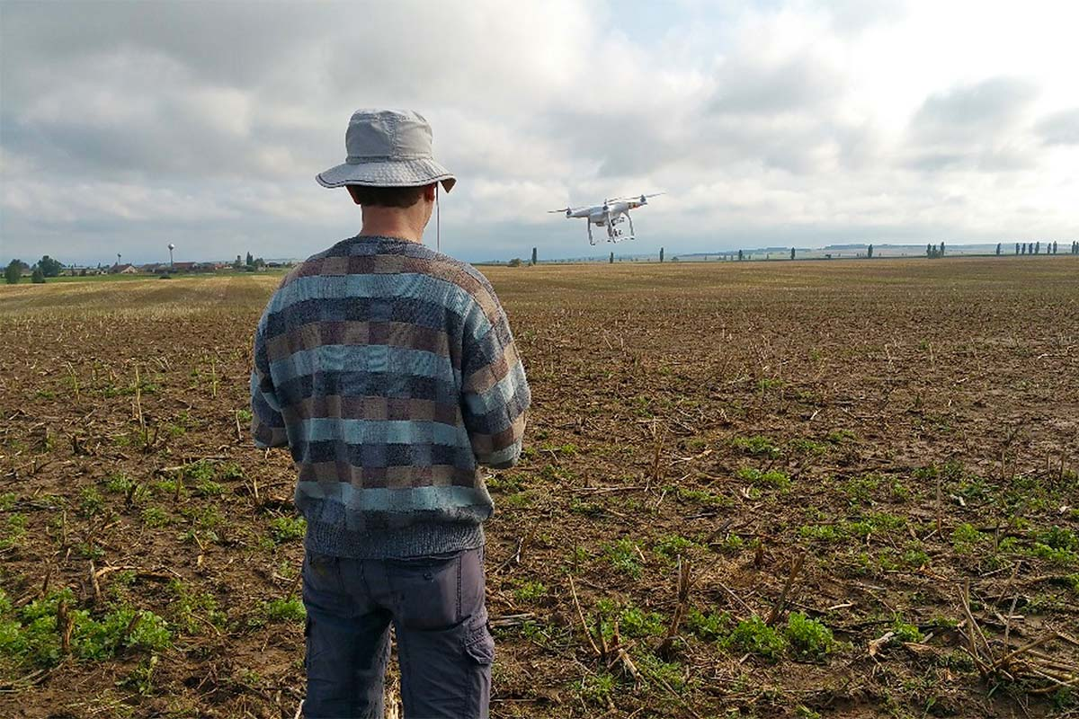 A man testing a drone on a field