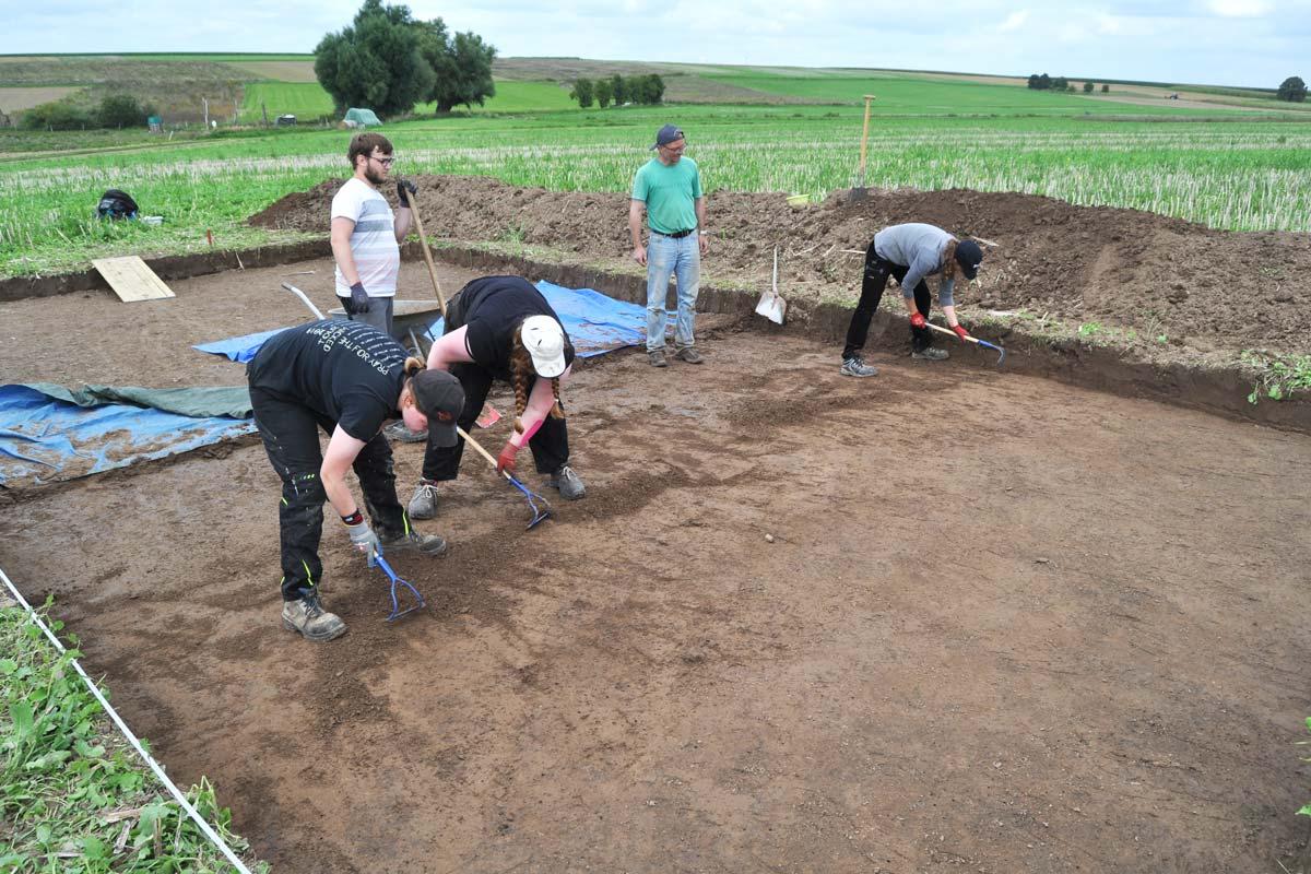 Personen bei der Bearbeitung einer Grabungsfläche