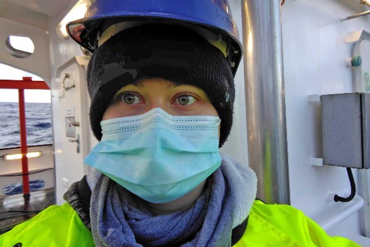 Frau mit Maske und Helm auf einem Schiff