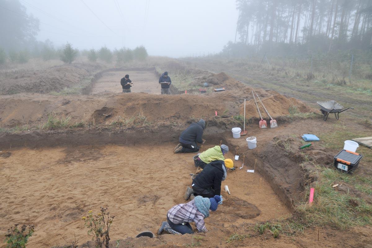 Zwei Grabungsflächen mit Personen im Nebel