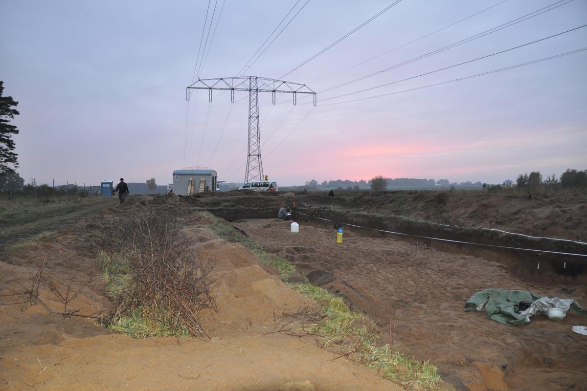 Grabungsfläche mit Strommast im Hintergrund