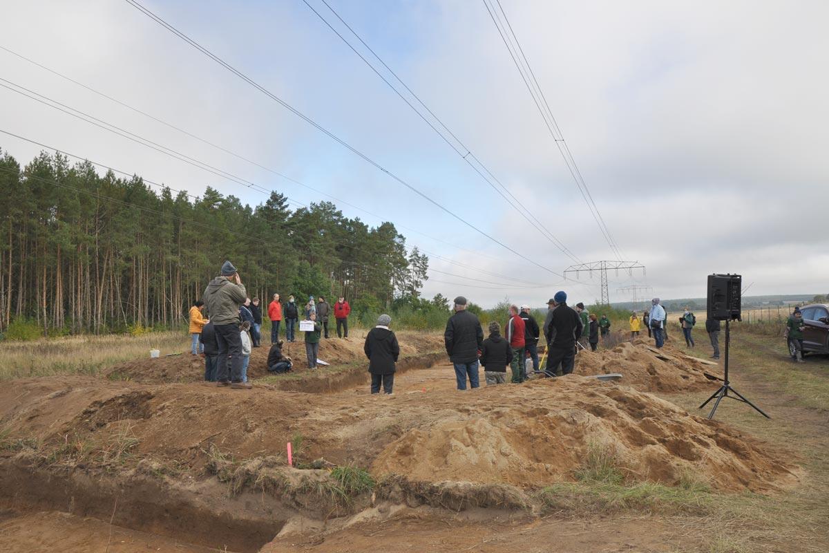 Viele Personen stehen um eine Grabungsfläche herum