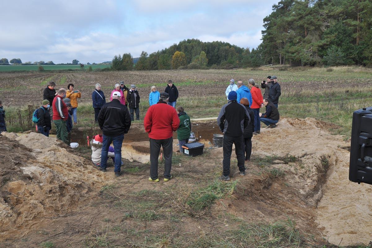 Mehrere Personen stehen am Rande einer Grabungsfläche