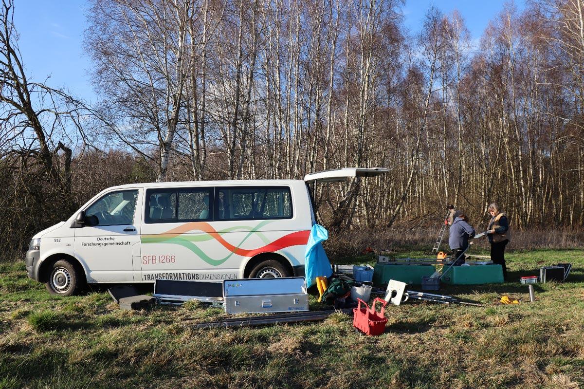 Fahrzeug mit 2 Personen und Grabungs-Utensilien